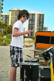Teen boy with drums on the beach royalty free stock photography
