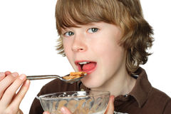 Teen boy eating a bowl of cereal Royalty Free Stock Image