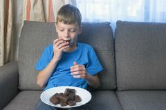 Teen boy is eating chocolate candies sitting on the sofa. Concept of unhealthy eating. royalty free stock photography