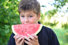 Teen boy eating watermelon in nature Stock Photography