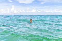 Teen boy enjoys swimming in the ocean Stock Photo