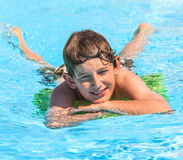 Teen boy enjoys swimming in a pool Stock Photo