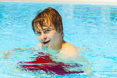 Teen boy enjoys swimming in a pool Royalty Free Stock Photography