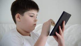 Teen boy enjoys  tablet indoors stock video footage