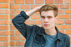 Teen boy face portrait posing stylish modern with hand up on hai Royalty Free Stock Photo