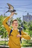 Teen boy feeds pigeons on city street Stock Photos
