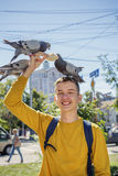 Teen boy feeds pigeons on city street. Summer day Stock Image