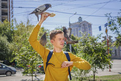 Teen boy feeds pigeons on city street stock photo