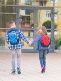 Teen boy and girl back to school. Happy children - boy and girl with backpack on the first or last school day - outdoor portrait, back view. Excited to be back stock photography