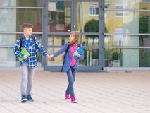 Teen boy and girl back to school. Happy children - boy and girl with backpack on the first or last school day - outdoor portrait, back view. Excited to be back royalty free stock photos