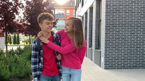 Teen boy and girl back to school. Two schoolchildren go to school with backpacks. Cute children - teen girl and boy with bags Back to school. Concepts of friends stock video footage