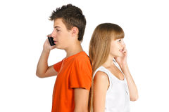 Teen boy and girl chatting on cell phones Royalty Free Stock Images
