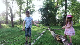 Teen boy and girl child walking on a log. Brother and sister helping each other to walk on the balance beam. Old overgrown park. Summer sunny evening stock footage