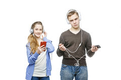 Teen boy and girl with headphones. Beautiful teen age boy and girl in casual clothes standing on white background listening to music in headphones. School Royalty Free Stock Photography