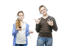 Teen boy and girl with headphones. Beautiful teen age boy and girl in casual clothes standing on white background listening to music in headphones. School Royalty Free Stock Image