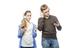Teen boy and girl with headphones. Beautiful teen age boy and girl in casual clothes standing on white background listening to music in headphones. School Stock Image