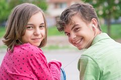 Teen boy and girl with headphones. Happy teenage boy and girl with headphones are using gadget, talking and smiling while sitting on the stairs outdoors. Young Stock Photo