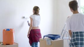 Children painting wall in room. Teen boy and girl makes repairs in new flat. Sister and brother painting wall in apartment room. Children paints the wall, using stock video