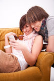 Teen boy and girl with a phone. And armchair Stock Photo