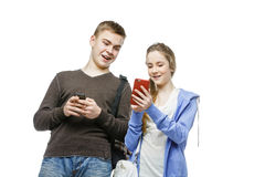Teen boy and girl standing with mobile phones Royalty Free Stock Image