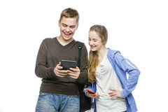 Teen boy and girl standing with mobile phones. Beautiful teen age boy and girl in casual clothes holding mobile phones. School children texting using cellulars Royalty Free Stock Photos