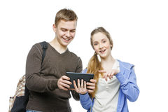 Teen boy and girl standing with mobile phones. Beautiful teen age boy and girl in casual clothes holding mobile phones. School children texting using cellulars Royalty Free Stock Photography