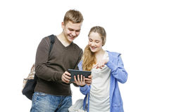Teen boy and girl standing with mobile phones. Beautiful teen age boy and girl in casual clothes holding mobile phones. School children texting using cellulars Stock Photography