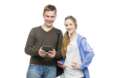 Teen boy and girl standing with mobile phones. Beautiful teen age boy and girl in casual clothes holding mobile phones. School children texting using cellulars Stock Photos
