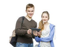 Teen boy and girl standing with mobile phones. Beautiful teen age boy and girl in casual clothes holding mobile phones. School children texting using cellulars Royalty Free Stock Images