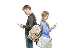 Teen boy and girl standing with mobile phones. Beautiful teen age boy and girl in casual clothes holding mobile phones. School children texting using cellulars royalty free stock photo