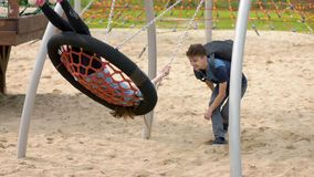 Teen boy and girl on swing. Happy two children with backpacks riding on swing in playground outdoors. Cute teen boy boy pushes girl on swing. Teenagers having stock video