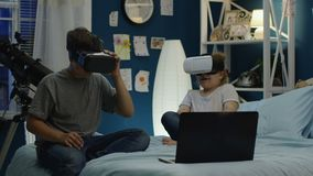 Kids playing video game in VR goggles on bed. Teen boy and girl wearing VR goggles while sitting on bed at home with laptop near and gaming together at night stock footage