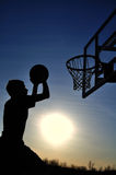 Teen Boy Going For The Dunk. Silhouette of a teen boy going for a dunk Royalty Free Stock Image