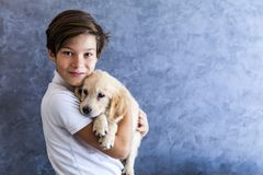 Teen boy with golden retriever. Portrait of teen boy with golden retriever by the wall royalty free stock images