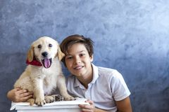 Teen boy with golden retriever. Portrait of teen boy with golden retriever by the wall stock photography