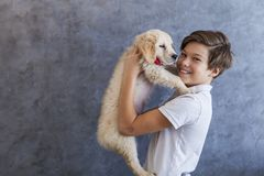 Teen boy with golden retriever. Portrait of teen boy with golden retriever by the wall royalty free stock image