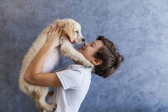 Teen boy with golden retriever. Portrait of teen boy with golden retriever by the wall royalty free stock photo