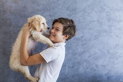Teen boy with golden retriever. Portrait of teen boy with golden retriever by the wall stock photo