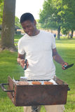 Teen Boy Grilling Hamburgers at a Park. Teenage boy smiles as he cooks hamburger patties on a barbecue grill at a park. Vertical format Royalty Free Stock Photography