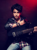 Teen boy with guitar. Talented serious teen boy with guitar over dark red background, playing on musical instrument, happy adolescence lifestyle Stock Photo