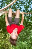 Teen boy hanging from a tree in a summer garden Stock Images