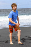 Teen boy has fun at the black volcanic beach Royalty Free Stock Images