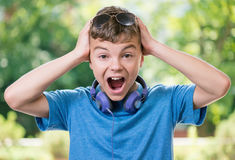 Teen boy with headphones. Beautiful shocked teen boy with headphones and sunglasses Royalty Free Stock Photos