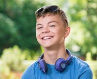 Teen boy with headphones. Beautiful smiling teen boy with headphones and sunglasses Royalty Free Stock Image