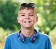 Teen boy with headphones. Beautiful smiling teen boy with headphones and sunglasses Stock Photos