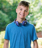Teen boy with headphones. Beautiful smiling teen boy with headphones and sunglasses Stock Photography