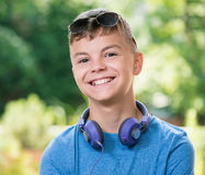 Teen boy with headphones. Beautiful smiling teen boy with headphones and sunglasses Royalty Free Stock Photography