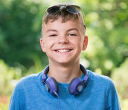 Teen boy with headphones. Beautiful smiling teen boy with headphones and sunglasses. Happy child having fun in park on green background Stock Images