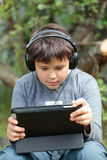 Teen boy in headphones with pad. Teenager boy in headphones using tablet PC. He listening to music or watching movie Royalty Free Stock Photo