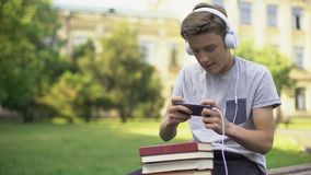 Teen boy in headphones playing mobile game instead of homework, procrastination. Stock footage stock video